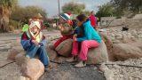 ילדים יושבים על אבנים