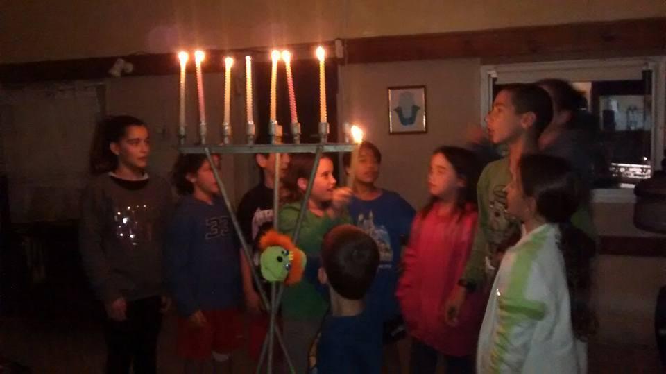 ילדים מדליקים נרות חנוכה